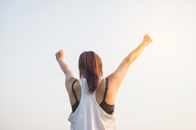 a woman with positive self-talk raising hands in a sign of victory